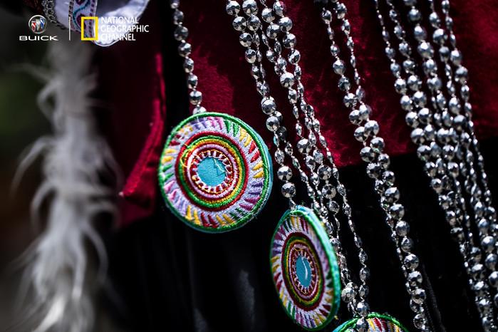 李院长还介绍了纳西族妇女的传统服饰,衣裙为麻布制造,过去纳西族妇女需要经常背着箩筐上山采集,所以后背都有一张完整的羊皮,羊皮里面是毛,既能保护背部,又能在高寒地区防寒,还有一种用途就是在山上歇息的时候可以拆下来垫着坐下。系于腰部的七个彩色圆形装饰叫做七星,黑白花纹的腰带都是手工缝制的花纹,仔细一看,有云,有花,有蝴蝶,还有跳舞的小人,说明纳西族是一个崇拜自然的民族。不过李院长也表示,现在她们已经不再穿传统的服装了,一来是不方便,二来因为现在手工缝制业息微。过去,纳西族是全民信奉东巴教,说到大时代现代化的