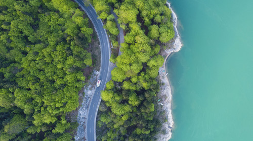 Aerial view on turquoise Lake Sylvenstein and forest with road on the bay. Germany, Bavaria, Lake Sylvenstein