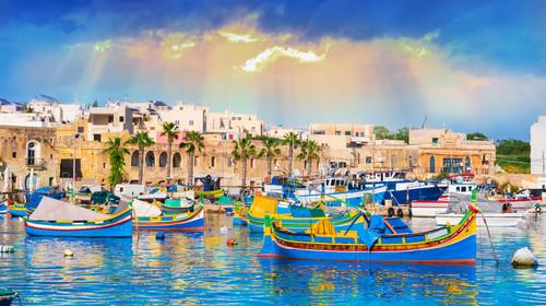 Marsaxlokk village harbor of Malta, illuminated by sunset light