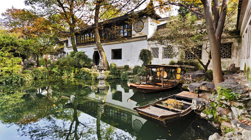 Historic traditional botanic garden in Chinese city Suzhou interior view of architecture around still pond with boats and trees