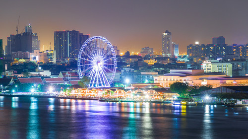Aerial view of Ferris wheel and Bangkok city night light at Chao Phaya riverfront. Ferris wheel is an important point