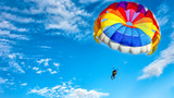Two men are flying in the blue sky using a colorful parachute.