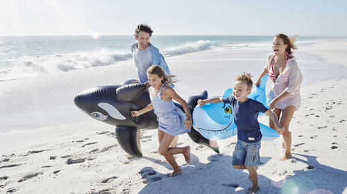 Young family carrying inflatable pool toys while running on the beach