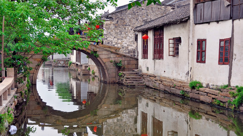 Zhouzhuang, a Shanghai tourist attraction. Old houses and bridge reflection in a village canal.